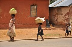 African family carrying banana basket on the head. In a traditional village in Madagascar, mother and little daughter royalty free stock photography