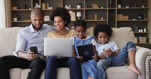 African family sit on sofa using diverse electronic devices
