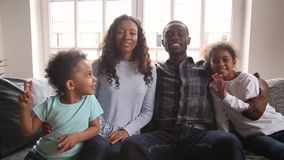 African family sitting on couch waving hands looking at camera