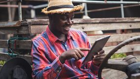Free African Farmer Using Tablet And Smiling While Sitting In The Tractor.Agriculture Or Cultivation Concept Stock Images - 216332554