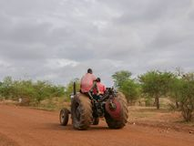 African farmers drive a tractor stock photo
