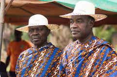African fashion. Close-up of two old people standing with hat, dressed in loincloth shirt and doubled loincloth covering their shoulder to the left. It is this Royalty Free Stock Photo