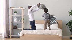 African father playing pillow fight with little son. African father enjoying pillow fight with little mixed race son on bed at home, carefree funny older younger stock footage