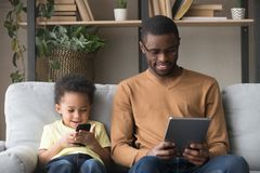Addicted of gadgets african dad and son sitting on couch. African father in glasses holds tablet read media spend free time with little adorable son, kid use stock photo
