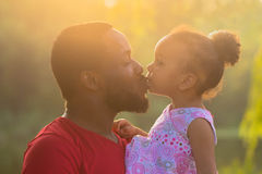 African father hugging and kissing a baby daughter. Happy fatherhood concept Royalty Free Stock Photo
