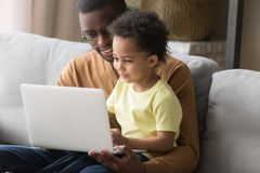 African father and little son sitting on couch with notebook stock photo