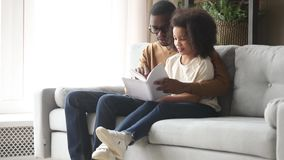 African father reading book to daughter sitting together on couch