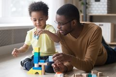 African father and son play with colourful toy blocks stock images