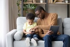African father helping little son explain new app or game royalty free stock images