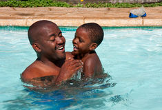 African father son swim. African black man and son swimming in bright sunlight in pool Stock Image
