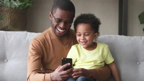 African father spend time with son having fun using smartphone