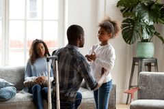 African father talking to upset kid daughter saying goodbye. African american father talking to upset mixed race kid daughter saying goodbye to sad preschool royalty free stock image