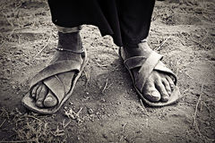 African Feet. The old, dirty wrinkled feet of an African Maasai woman in worn leather sandals Royalty Free Stock Photo