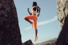 African female athlete jumping and stretching. Over rocks outdoors. Healthy and tough woman exercising Royalty Free Stock Photos