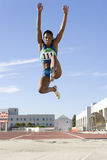African female athlete mid-air during long jump Stock Image