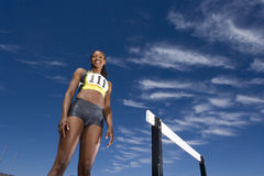 African female athlete standing near hurdle Stock Image