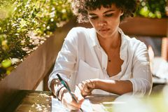 African female at cafe writing notes stock photo