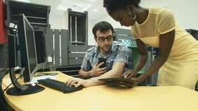 African female colleague with tablet asking busy man to sign document on screen. Busy man talking over cell and typing on computer keyboard while signing on stock footage