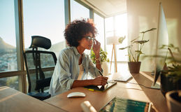 African female designer busy working at her desk. Creative woman working with graphics tablet and looking at desktop monitor in office Royalty Free Stock Photo