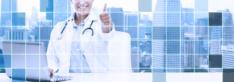 African female doctor with laptop shows thumbs up Stock Photo
