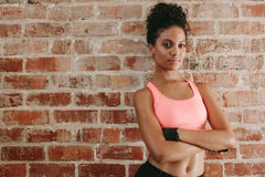 African female fitness model in gym. Portrait of young african woman in sports bra standing against brick wall with her arms crossed. Female fitness model in gym royalty free stock image