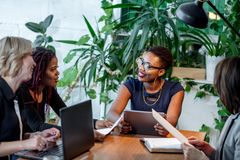 African female manager consulting women at her office promising benefits royalty free stock photo