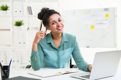 African female in office. Happy smiling african american female using laptop on office desktop with notepad and other stationery items Stock Images