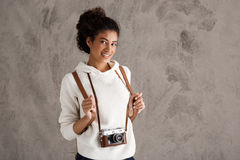 African female photograph smiling, holding camera over beige background. Stock Photography