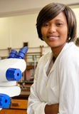African female researcher smiles sitting next to microscope. Stock Photography