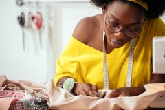 Sewing fabric with needle at seamstress workplace. African female sewing fabric with needle at seamstress workplace stock photos