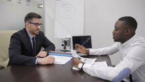 African financial analytic is explaining his point on investments profit to his boss in co-working room. The businessman in glasses and suit with tie is stock footage