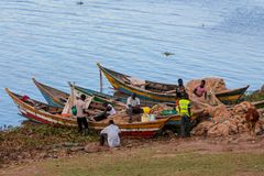 African fisher men on the lake shore near boat preparing the net for fishing. Fishermen working hard in Africa at lake Victoria Stock Image