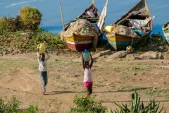 African fisherman boat and children at lake shore. African fisherman boat and children carry water at lake shore of Victoria lake in Africa Royalty Free Stock Images