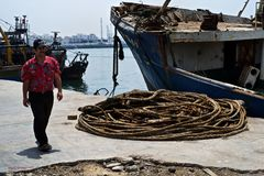 African fishing boats docked in a harbor next to a pile of coiled rope stock photos