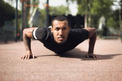 African Fit Man Doing Push-Ups In Park. Looking At Camera stock image