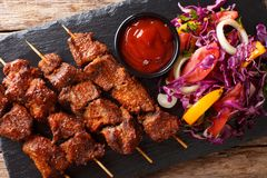 African food: spicy suya kebab on skewers with fresh vegetable s. Alad and ketchup close-up on the table. horizontal top view from above stock photos