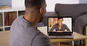 African friends video chatting on laptop. Two African friends video chatting on laptop royalty free stock photography