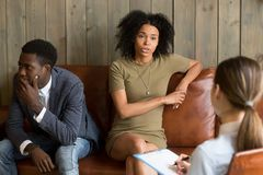 African frustrated wife talking to psychologist, family marriage. African frustrated wife talking to psychologist sitting on couch with husband, black unhappy Royalty Free Stock Photography