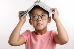 African funny girl with a book is making faces stock photography