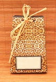 African gift bag with voucher. An African luxury hotel spa welcome gift bag on bamboo background with blank tag for the designers message Royalty Free Stock Image