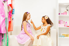 African girl applying perfume on her friend. While sitting on white sofa royalty free stock images