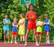 African girl with ball and teens standing behind Stock Photo