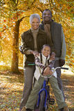 African girl on bicycle with grandparents in autumn Stock Photos