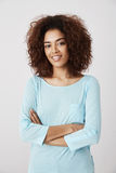 African girl in blue shirt smiling posing with crossed arms. royalty free stock photo