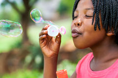 African girl with braids blowing bubbles. Stock Photography