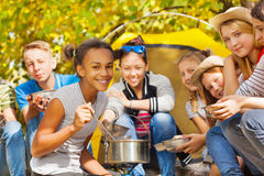 African girl cooks soup in pot at campsite Royalty Free Stock Image