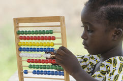 African girl counting on abacus in school. Little african girl counting on abacus frame on blurred background Stock Photo