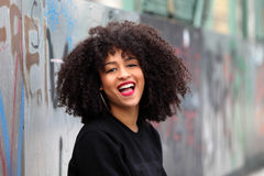 African girl with curly hair. Beautiful African woman on a bridge with graffiti royalty free stock images