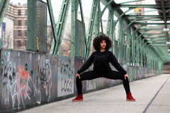 African girl with curly hair. Beautiful African woman doing acrobatic pose on a bridge stock photo