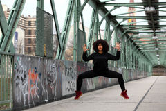 African girl with curly hair. Beautiful African woman doing acrobatic pose on a bridge royalty free stock photo